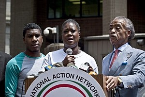 Trayvon Martin's mother Sybrina Fulton speaks at a podium as Trayvon Martin's brother Jahvaris Fulton (L) and Rev. Al Sharpton attend a rally