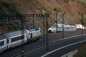 A train passes the wreckage of the high speed Renfe train