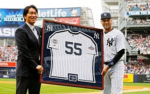 Derek Jeter #2 of the New York Yankees presents former Yankee Hideki Matsui a framed jersey during during a pre game ceremony honoring Matsui