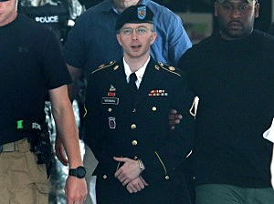 U.S. Army Private First Class Bradley Manning (C) is escorted by military police as he leaves his military trial after he was found guilty of 20 out of 21 charges
