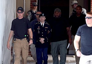 U.S. Army Private First Class Bradley Manning (C) is escorted by military police as he leaves his military trial