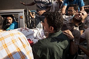 An injured supporter of deposed Egyptian President Mohammed Morsi is carried into the al-Sednawi hospital near Ramses Square