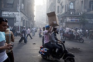 Supporters of deposed Egyptian President Mohammed Morsi carry supplies during violent fighting near Ramses Square
