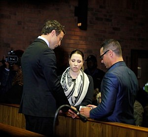 Oscar Pistorius (L) prays with his sister Aimee Pistorius and brother Carl Pistorius prior to his indictment hearing in Pretoria Magistrates Court