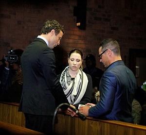 Oscar Pistorius (L) prays with his sister Aimee Pistorius and brother Carl Pistorius prior to his indictment hearing in Pretoria Magistrates Court