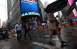 People walk past the NASDAQ MarketSite in Times Square