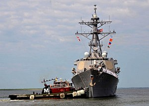The U.S. Navy guided-missile destroyer USS Ramage (DDG 61) is assisted by a tug boat as it pulls away from the pier at Naval Station Norfolk