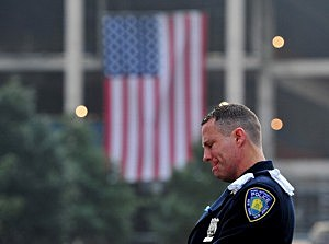 Daniel Henry, a Port Authority of New York/New Jersey police officer, pauses during a moment of silence at 9:01 am EDT, at the South reflecting pool of the 9/11 Memorial