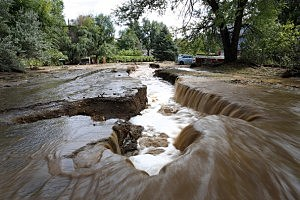 Water rushes down a flooded Topaz Street in Boulder, Colorado.