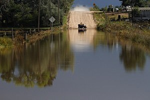 A couple on an ATV turn around at the edge of a flooded road in La Salle, Colorado.