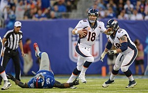 Peyton Manning #18 of the Denver Broncos gets away from defensive defensive tackle Shaun Rogers