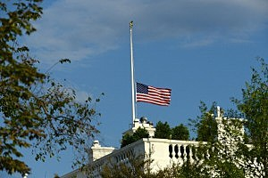 The U.S. flag is shown lowered to half-staff at the White House