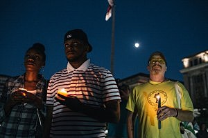 Brittany Carter, of Bowie, MD., (L) Jibri Johnson, of Landon, MD., (C) and Bryan Beard of Washington D.C. hold candles at a vigil for Navy Yard shooting victims