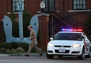 A member of the U.S. Navy walks away from the front gate of the Washington Naval Yard