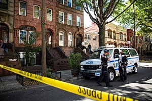 Policemen stand guard outside the home of Cathleen Alexis, the mother of Washington Navy Yard shooter Aaron Alexis in Brooklyn