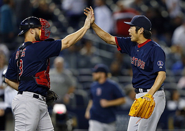 Catcher David Ross #3 and relief pitcher Koji Uehara #19 of the Boston Red Sox celebrate after defeating the New York Yankees