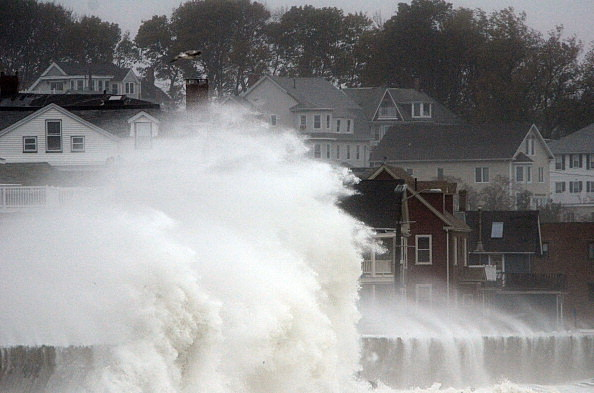 Waves crash over Winthrop Shore Drive in Winthrop, Mass.