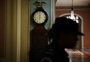 A Capitol Hill Police officer passes by the Ohio Clock which shows the time has just passed midnight on the Senate side of the U.S. Capitol