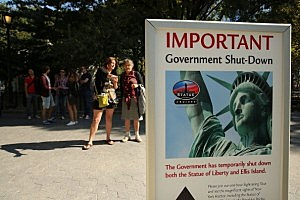 People look at a sign for informing that the Statue of Liberty is closed