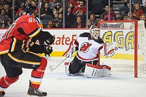 Martin Brodeur #30 of the New Jersey Devils makes a glove save against the shot of Lance Bouma #17 of the Calgary Flames