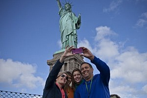 Tourists pose for pictures during a visit to the Statue of Liberty after it was reopened on Sunday