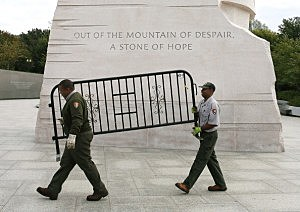 U.S. Park Service workers carry a barricade that was used to close the Martin Luther King Memorial
