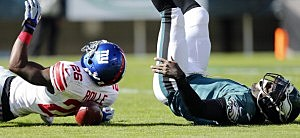 Michael Vick #7 of the Philadelphia Eagles fumbles as he is sacked by safety Antrel Rolle #26 of the New York Giants who is unaware that his lying on the ball