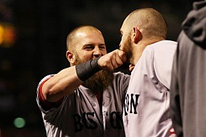 Mike Napoli #12 of the Boston Red Sox pulls teammate Jonny Gomes #5 beard after hitting a three run home run to left field