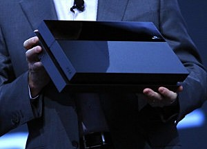Andrew House, President and Group CEO Sony Computer Entertainment Inc., holds up a Playstation 4