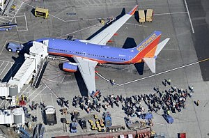 Evacuated passengers wait on the tarmac next to a Southwest Airlines passenger jet after a shooting at Los Angeles International Airport