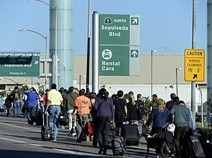 Arriving passengers walk out of Los Angeles International Airport (LAX) as the surrounding streets are still shut down after shooting