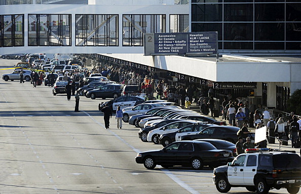 Stranded passengers return to Terminal 2 as normal operations slowly return after a shooting incident at Los Angeles International Airport
