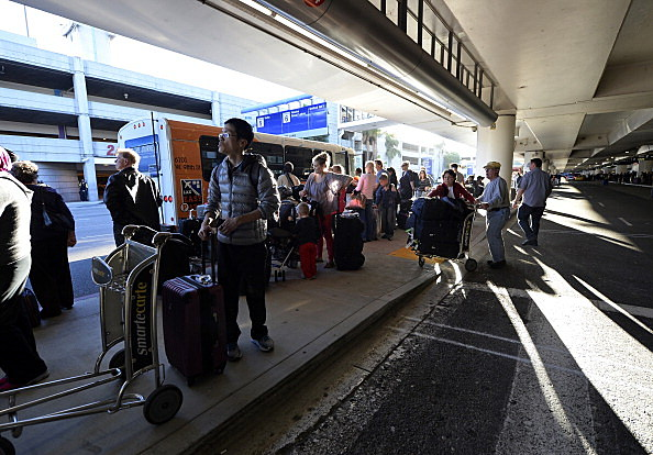 : Stranded passengers wait for buses to pick them up as normal operations slowly return after a shooting incident at Los Angeles International Airport (