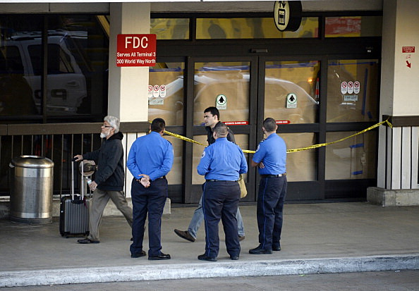 Transportation Security Administration workers stand in front of the blocked off Terminal 3 entrance