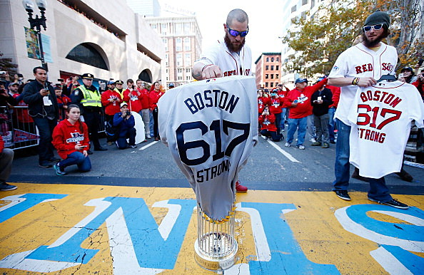 Jonny Gomes #5 and Jarrod Saltalamacchia #39 of the Boston Red Sox lay the World Series trophy and the 'Boston Strong 617' jerseys onto the finish line of the Boston Marathon on Boylston Street during the World Series victory parade