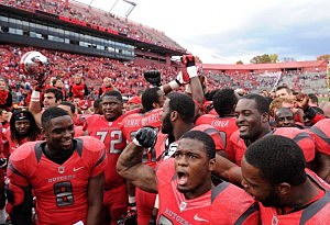 Johnathan Aiken #26 of the Rutgers Scarlet Knights, center, and Tejay Johnson #9, left, celebrate with their teammates following the game against the Temple Owls at High Point Solutions Stadium