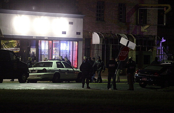 Detroit police officers investigate a shooting outside of a barber shop where ten people were shot