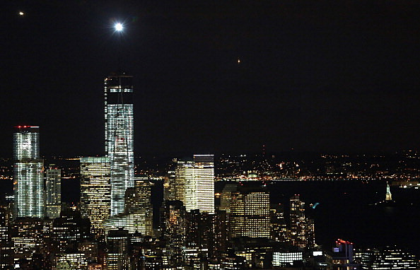 A newly lit beacon shines from atop the One World Trade Center