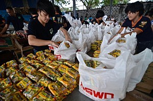 Bureau of Fire Protection volunteers pack relief goods bound for hard-hit areas of the southern Philippines at a government warehouse in Manila