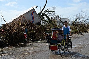 Residents pass by a damaged truck in the aftermath of typhoon Haiyan  in Tacloban City, Leyte, Philippines