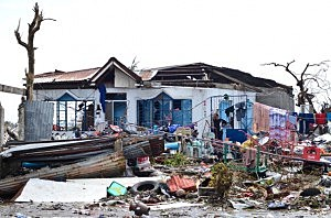A woman looks at what is left of her house in the aftermath of typhoon Haiyan on in Tacloban City, Leyte, Philippines