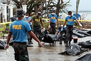 Members of the Philippine National Police carry body bags containing victims of Typhoon Haiyan