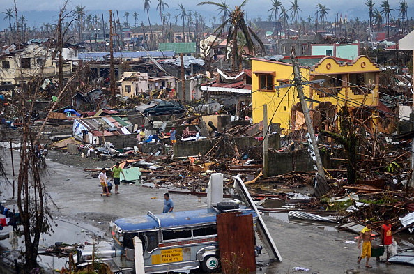 Surivors walk along a road through an area devastated by Typhoon Haiyan in Leyte, Philippines.