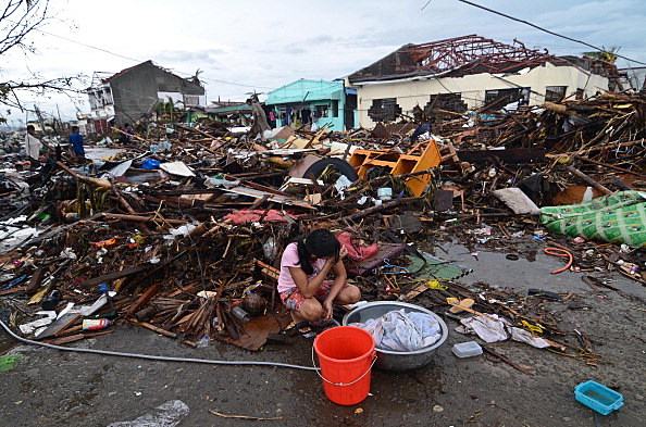 A girl pauses while washing clothes amongst the debris in an area devastated by Typhoon Haiyan in Leyte, Philippines.