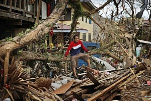 A man sits amongst the wreckage of his devastated home in the aftermath of Typhoon Haiyan in Tacloban, Leyte, Philippines.
