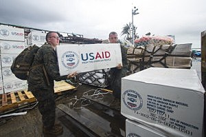 Corpsman 3rd Class Eric Chiarito (L) of Hyde Park, N.Y., and Marine Sgt. Jonathan Thornton, of Lake Havasu, Arizonia, load supplies onto a forklift at Tacloban Air Base