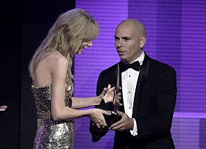 Taylor Swift (L) accepts award from host Pitbull onstage during the 2013 American Music Awards
