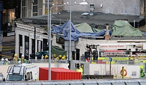 Rescue workers attend the scene at a pub on Stockwell Street where a police helicopter crashed on the banks of the River Clyde