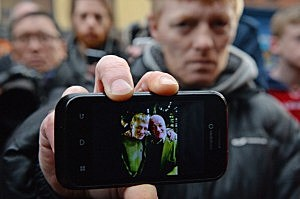 John McGarrigle junior, son of 60-year-old John McGarrigle senior, shows a camera phone picture of himself and his father who is missing after the Glasgow helicopter Clutha pub crash