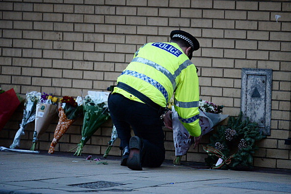 A police officer lays flowers near the scene where a police helicopter crashed into a pub on the banks of the River Clyde in Glascow, Scotland
